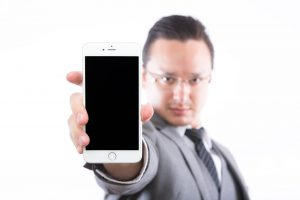 iPhoneを掲げる男性の図