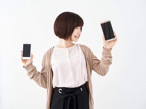 iphoneとスマホを迷っている女性